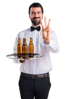 Camarero con botellas de cerveza en la bandeja contando tres