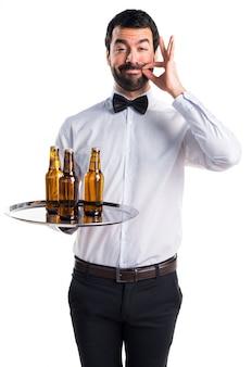 Camarero con botellas de cerveza en la bandeja haciendo gesto de silencio