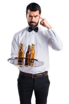Camarero con botellas de cerveza en la bandeja de pensamiento