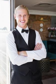 Camarero con los brazos cruzados en el restaurante