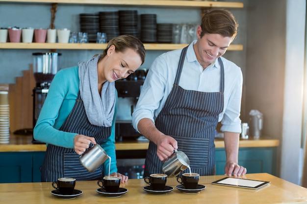 Camarero y camarera haciendo una taza de café en el mostrador de la cafetería