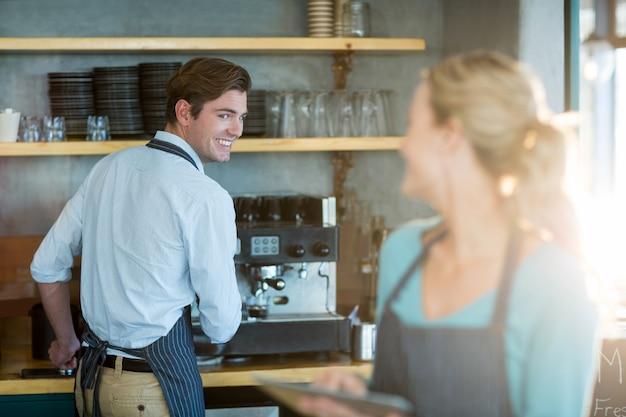 Camarero y camarera trabajando en la cocina en la cafetería