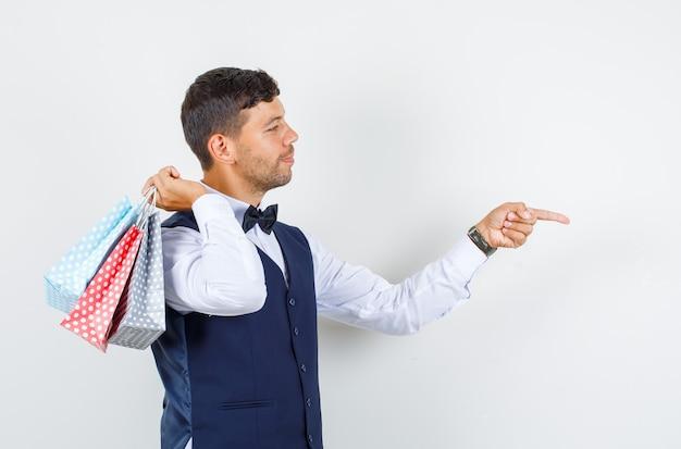 Camarero en camisa, chaleco apuntando al frente con bolsas de papel y con aspecto alegre.