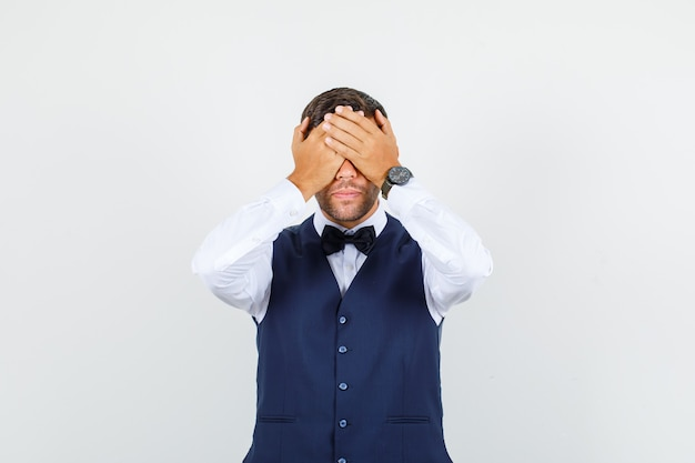 Camarero en camisa, chaleco cubriendo los ojos con las manos y mirando serio, vista frontal.