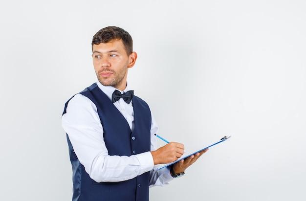 Camarero en camisa, chaleco mirando hacia atrás mientras toma notas en el portapapeles y mira pensativa, vista frontal.