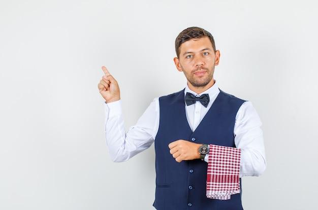 Camarero en camisa, chaleco, pajarita apuntando con el dedo hacia arriba y mirando confiado, vista frontal.