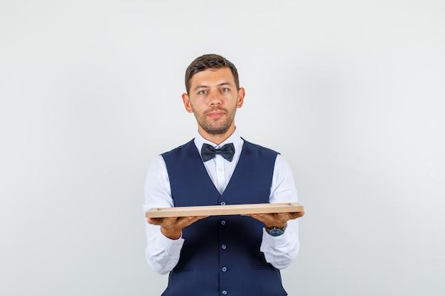 Camarero en camisa, chaleco sosteniendo bandeja de madera y mirando enfocado, vista frontal.