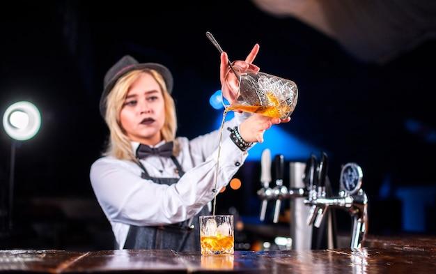 Camarero chica hace un cóctel en la taberna