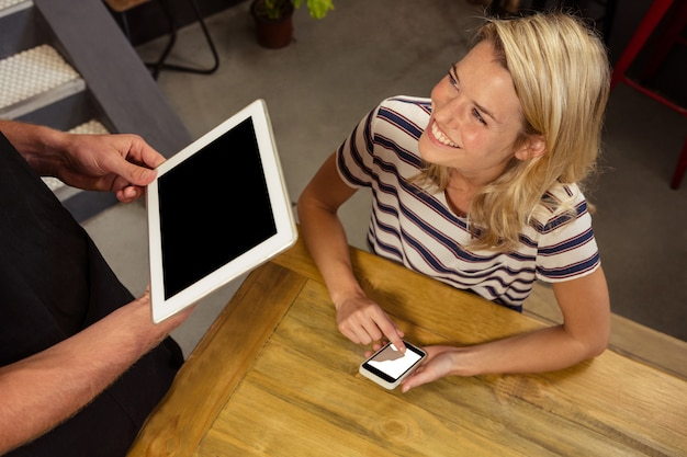 Camarero y cliente usando laptop y tableta digital