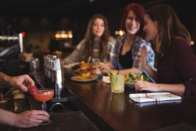 Camarero con cóctel en barra de bar