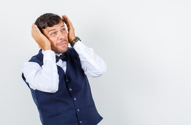 Camarero cogidos de la mano cerca de la cabeza en camisa, chaleco y mirando asustado, vista frontal.