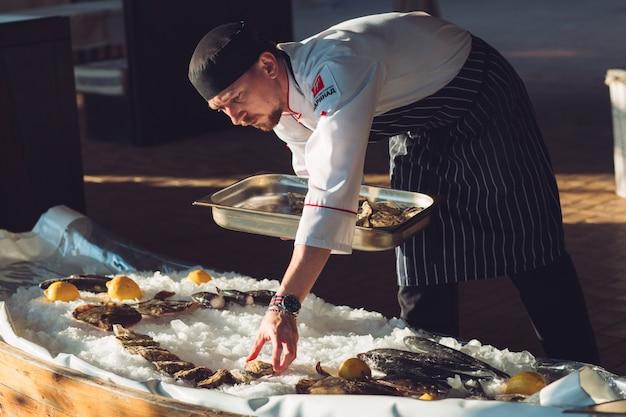 El camarero coloca los mariscos.