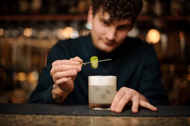 Camarero decorando una copa de cóctel con un pepino en un pincho de madera