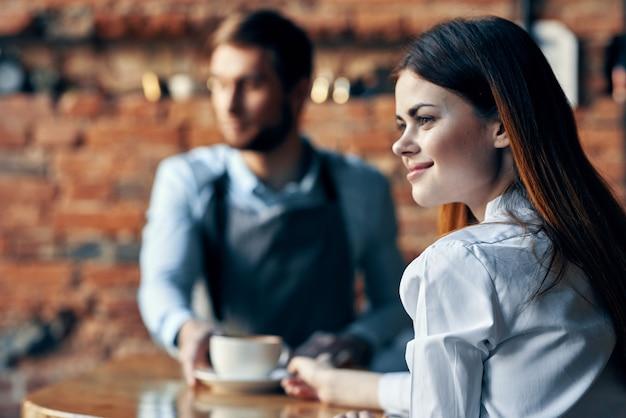 Camarero en delantal gris se sienta en la mesa y el cliente con una taza de café modelo interior de pared de ladrillo
