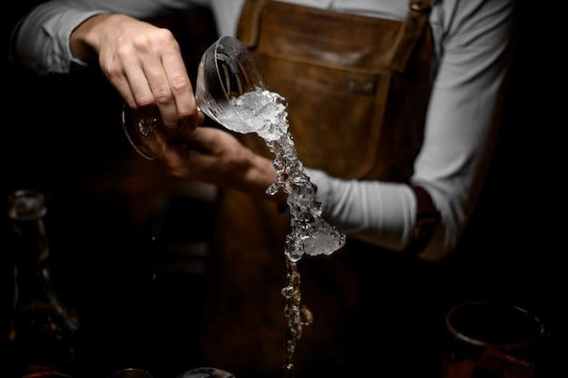 Camarero derrama hielo derretido del vaso