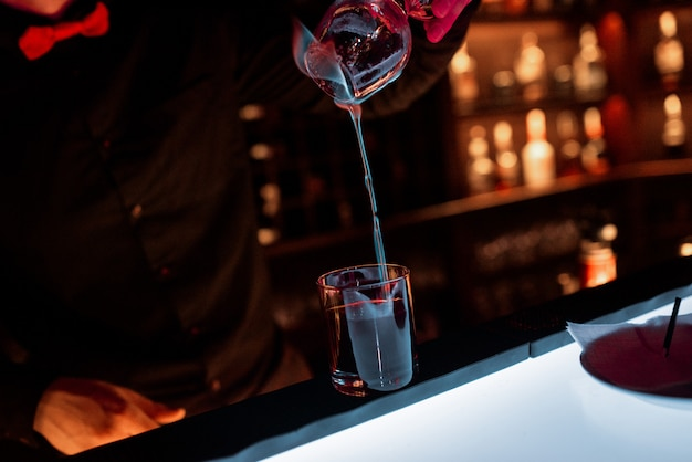 El camarero, detrás del bar, prepara un cóctel en llamas.