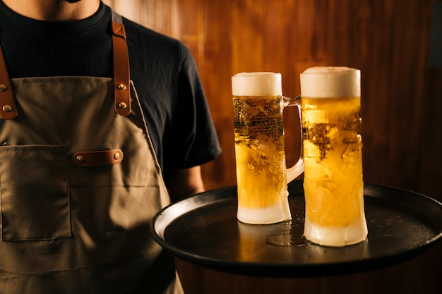 Camarero con dos jarras de cerveza fría en la bandeja