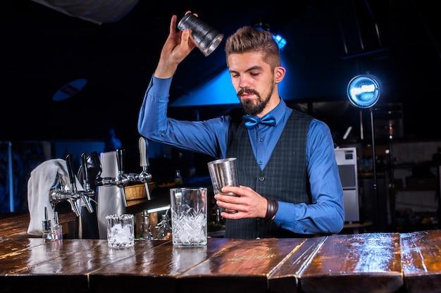 Camarero experto vertiendo bebida alcohólica fresca en los vasos en la discoteca