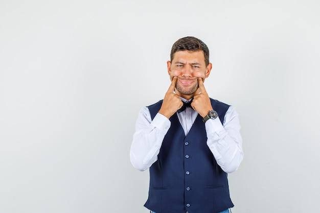 Camarero forzando una sonrisa en la cara con los dedos en camisa, chaleco y aspecto sombrío. vista frontal.