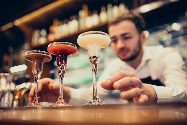 Camarero guapo haciendo beber y cócteles en un mostrador