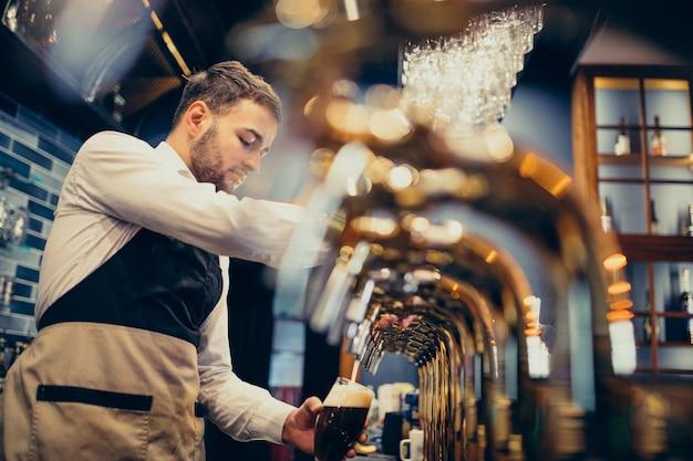 Camarero guapo vertiendo cerveza en pub