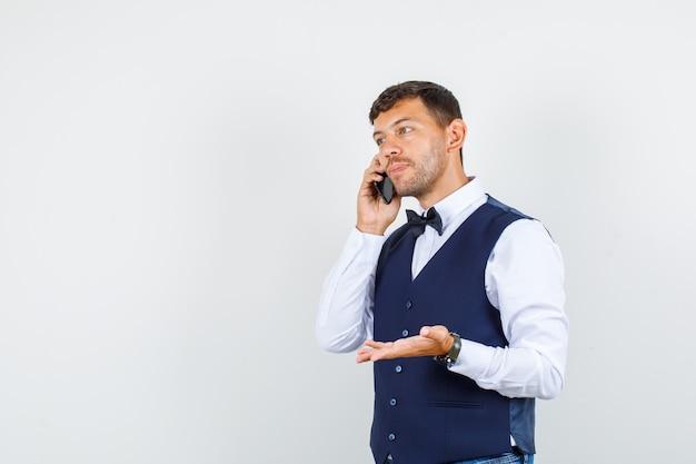 Camarero hablando por teléfono inteligente con signo de mano en camisa, vista frontal del chaleco.