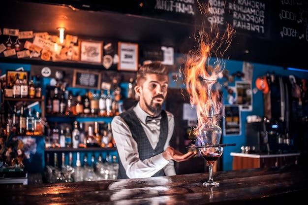 El camarero hace un cóctel en la cervecería.