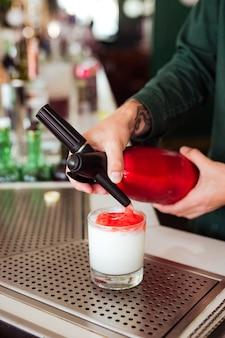 Camarero haciendo un cóctel en el bar: agregando espuma de fresa en una bebida con un sifón