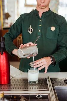 Camarero haciendo un cóctel en el bar: vertiendo una bebida de una coctelera a través de un colador en un vaso bajo