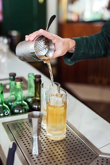 Camarero haciendo un cóctel en el bar: vertiendo una bebida de una coctelera en un vaso