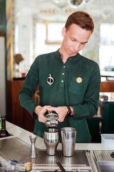 Camarero haciendo un cóctel, exprimiendo el jugo en una coctelera