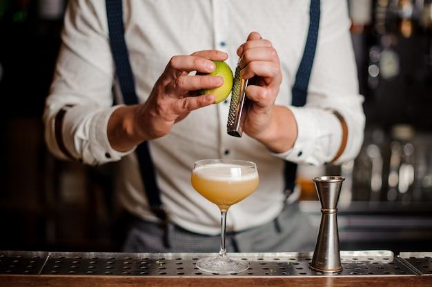 El camarero está haciendo un cóctel en el mostrador del bar sin rostro