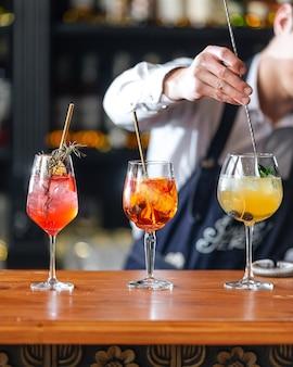 Camarero haciendo cócteles alcohólicos de frutas en el escritorio de madera