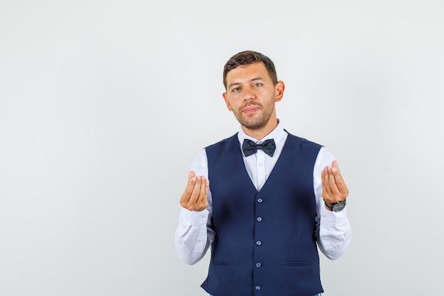Camarero haciendo gesto italiano y sonriendo en camisa, chaleco, pajarita vista frontal.