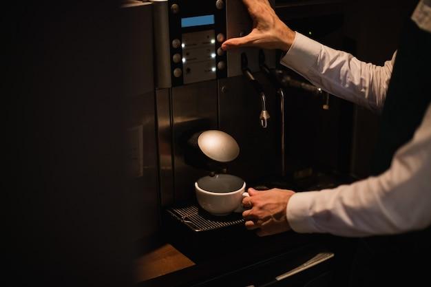 Camarero haciendo una taza de café de la máquina de café espresso