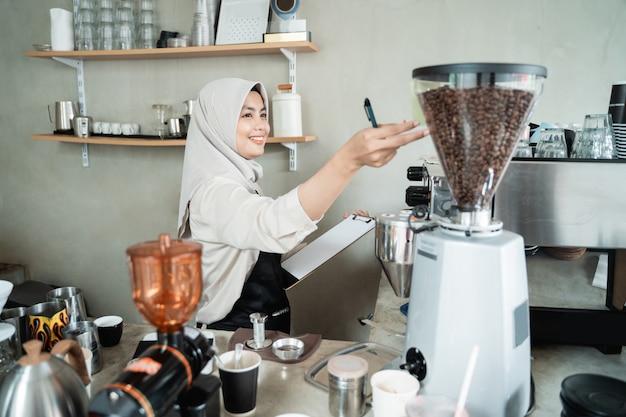 Camarero hembra tiene una máquina de café