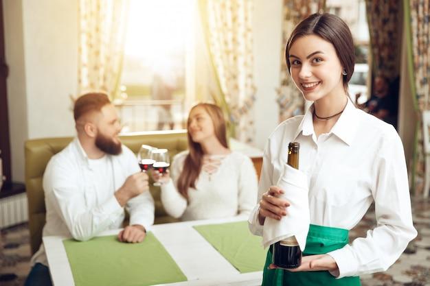 El camarero hermoso de la muchacha sostiene la botella abierta de vino