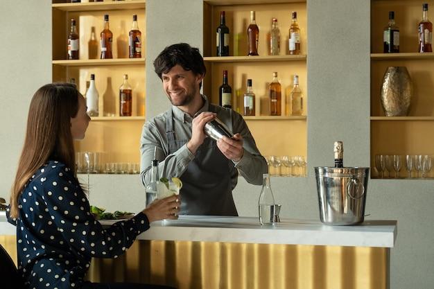 Camarero de hombre trabajando preparando cócteles en el bar hablando con su cliente mujer