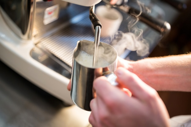 Camarero humeando leche en la cafetera
