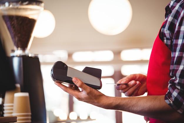 Camarero insertando la tarjeta de crédito del cliente en la máquina de tarjetas de crédito