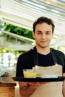 Camarero joven que sostiene la bandeja.