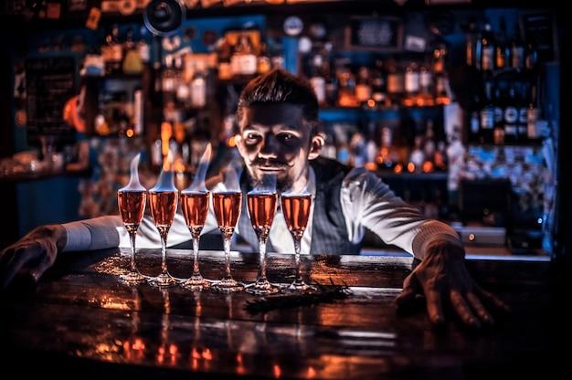 Camarero joven vertiendo bebida alcohólica fresca en los vasos en la barra del bar