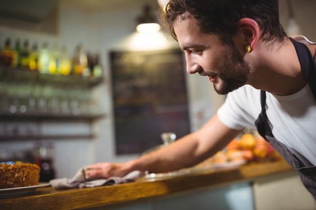 Camarero limpiando contador con la servilleta en la cafetería ©
