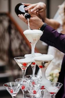 El camarero llena la fuente de champán pirámide de copas.