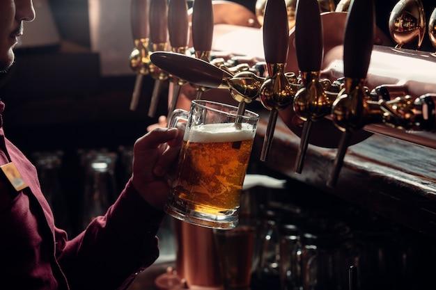 El camarero llena la jarra de cerveza del grifo de cerveza