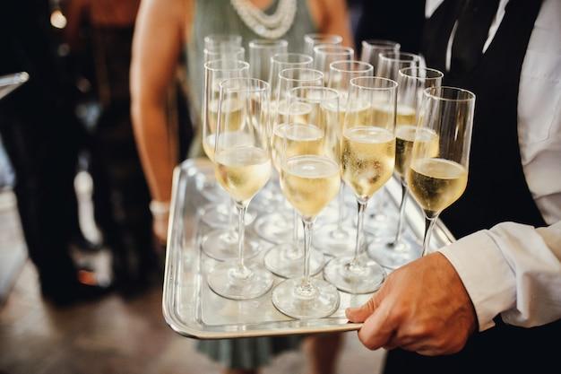 Camarero lleva copas con champaña fría.