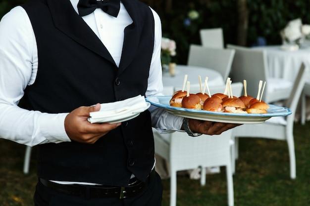 Camarero lleva placa con deliciosos aperitivos