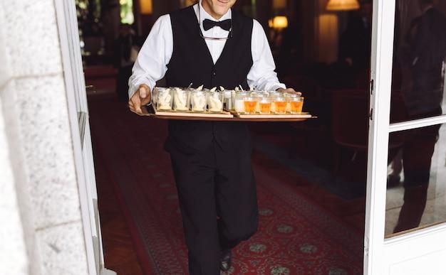 Camarero lleva plato con bocadillos caminando al patio trasero.