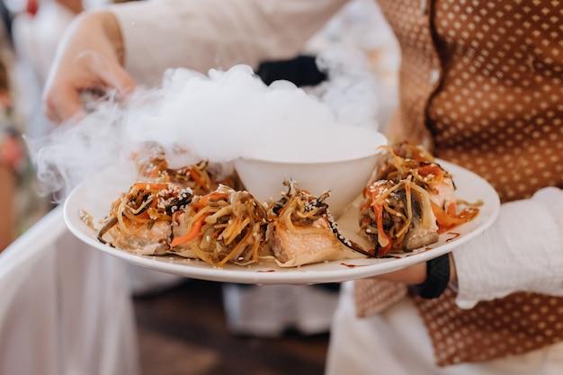 Camarero lleva un plato con comida delicada porción