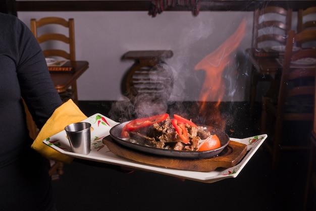 Camarero llevando bandeja con carne en llamas.